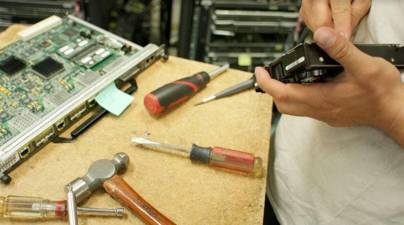IT person working on hardware with tools