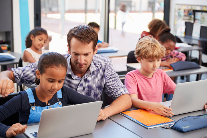 Teacher helping young students using laptops in class